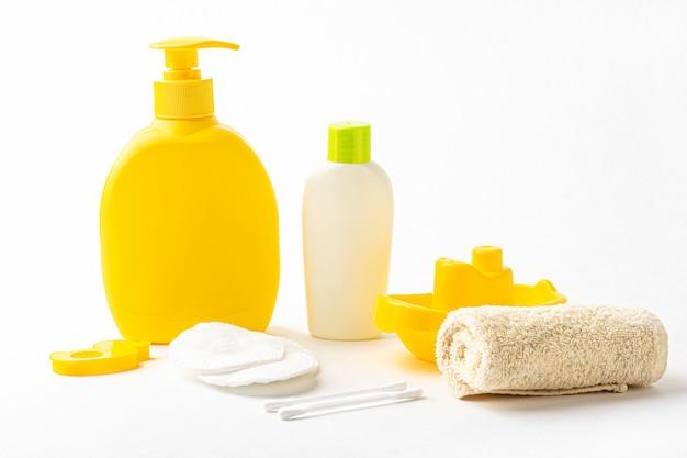 Botella de champú amarilla, toalla, almohadillas de algodón y barco de juguete en blanco.