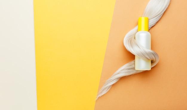 Botella de champú naranja con rizo de cabello rubio. cosméticos para el tratamiento de la higiene del cabello