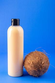 Una botella de champú de plástico de color crema con vista frontal puede con tapa negra aislada junto con coco en el fondo azul cosméticos belleza cabello