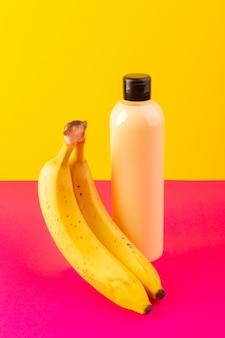 Una botella de champú de plástico de color crema vista frontal puede con tapa negra aislada junto con plátanos en el fondo de color rosa-amarillo cosméticos belleza cabello
