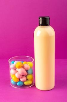 Una botella de champú de plástico de color crema con vista frontal puede con tapa negra y caramelos de colores aislados sobre el fondo morado cosméticos belleza cabello