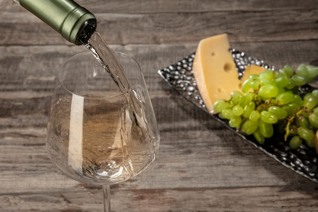 Una botella y una copa de vino blanco con frutas sobre mesa de madera