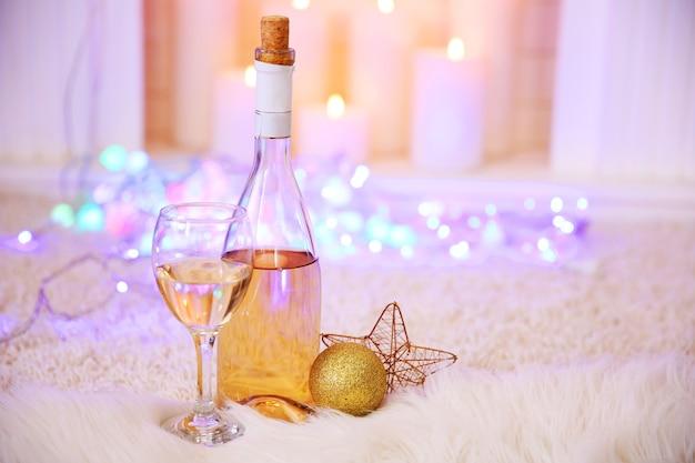 Botella y copa de vino con decoración navideña contra el fondo de luces de colores bokeh