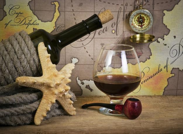 Botella y copa de vino en el fondo de mapas antiguos