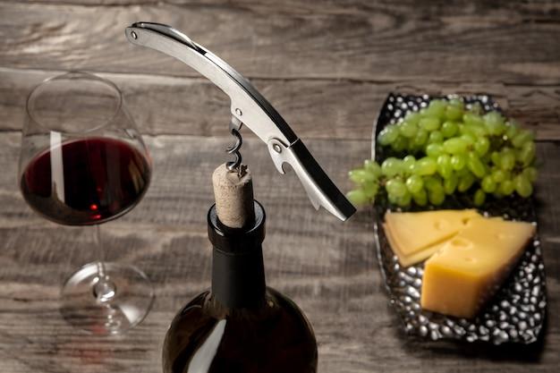 Una botella y una copa de vino tinto con frutas sobre mesa de madera