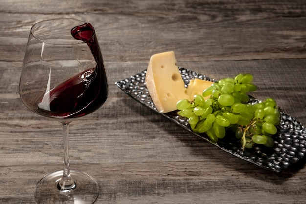 Una botella y una copa de vino tinto con frutas sobre superficie de madera desgastada