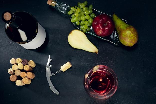Una botella y una copa de vino tinto con frutas sobre la superficie de piedra oscura