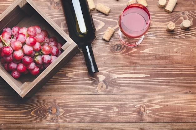 Botella y copa de vino con uvas sobre fondo de madera