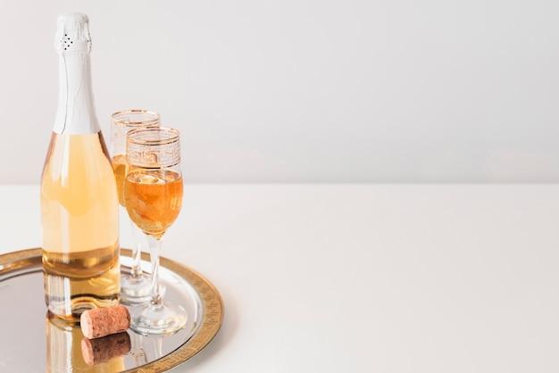 Botella con copas de champaña en una bandeja