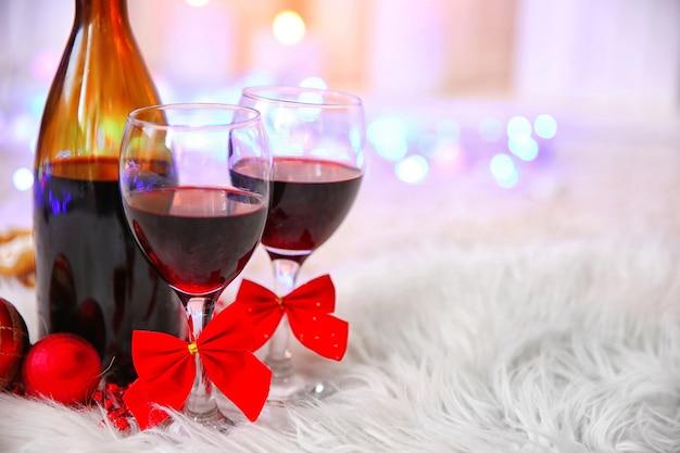 Botella y copas de vino con decoración navideña contra coloridas luces borrosas