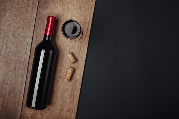 Botella de corchos de vino y copa de vino sobre fondo oxidado