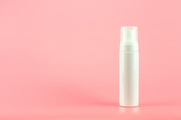 Botella cosmética plástica blanca de la loción en fondo rosado.