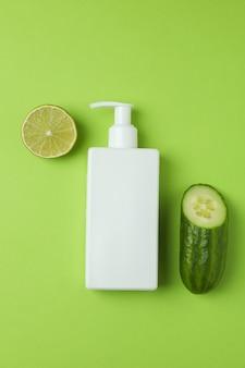 Botella con cosméticos, pepino y lima en superficie verde