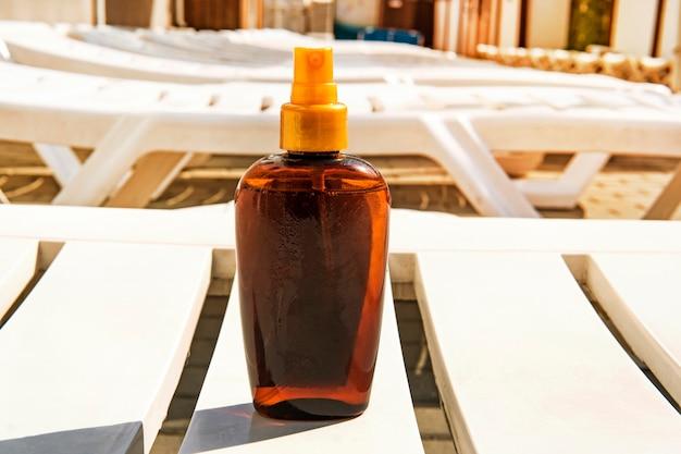 Botella con crema bronceadora en la tumbona. concepto de prevención de quemaduras solares y cáncer. copie el espacio. lugar para texto en botella. aceite bronceador.