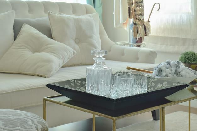 Botella de cristal y vasos en mesa con sofá beige en sala de estar