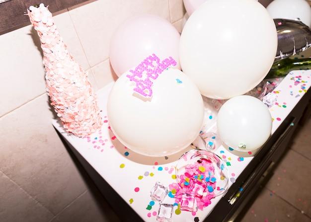 Botella cubierta de confeti rosa contra globo blanco.