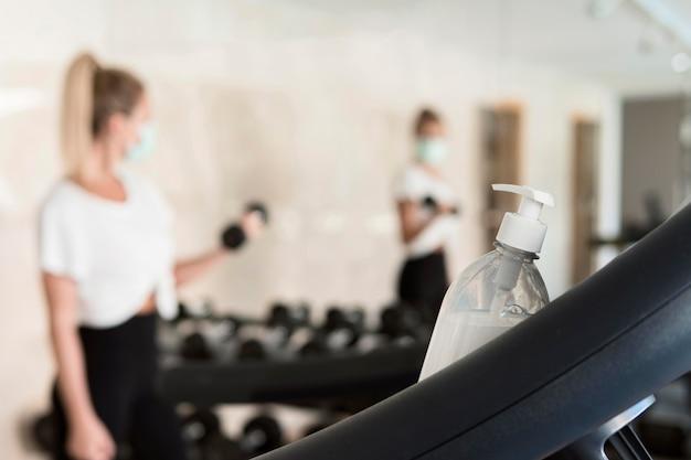 Botella de desinfectante de manos descansando sobre equipos de gimnasio