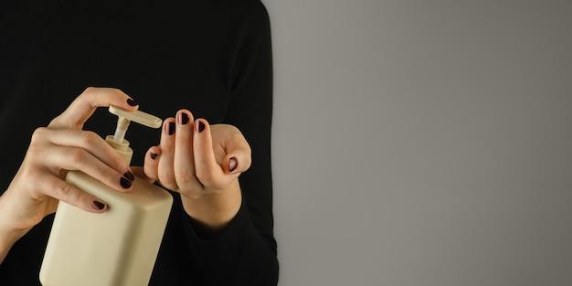 Botella de desinfectante para manos o jabón en manos femeninas