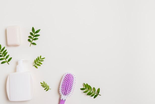Botella dispensadora; jabón y cepillo para el pelo con hojas sobre fondo blanco