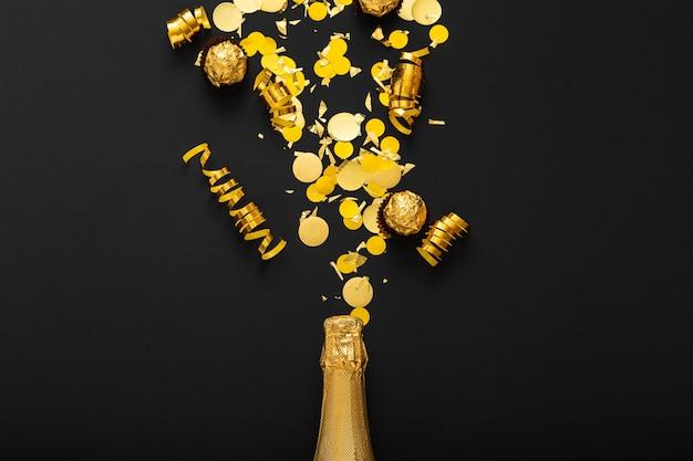 Una botella dorada de champán derrama destellos dorados.