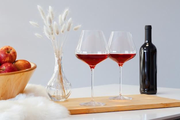 Botella y dos vasos de vino tinto, cuenco de madera con manzanas, florero sobre la mesa en la cocina moderna sobre fondo blanco.