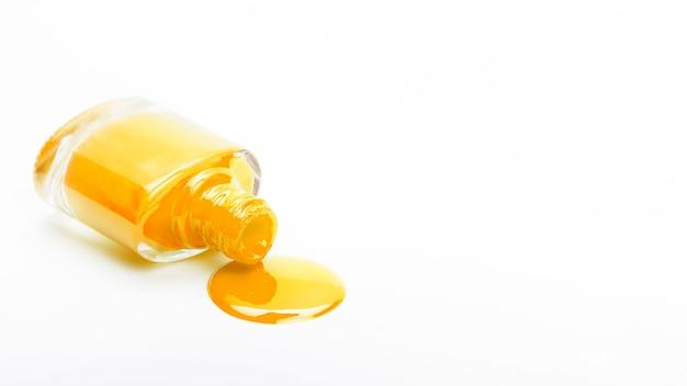 Botella de esmalte de uñas caído amarillo sobre fondo liso