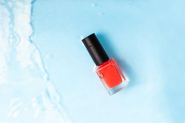 Botella de esmalte de uñas de color rojo sobre fondo azul agua. vista superior.