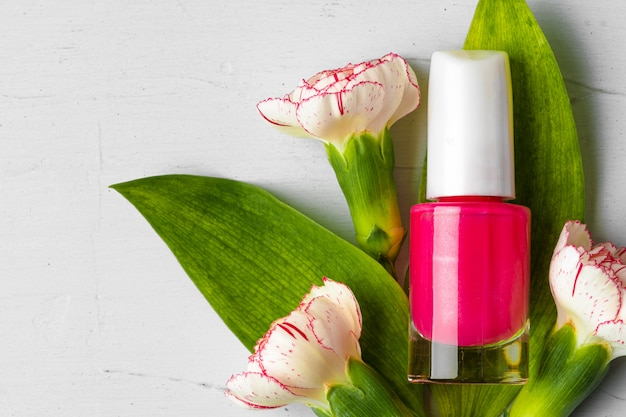 Botella de esmalte de uñas rosa con capullos