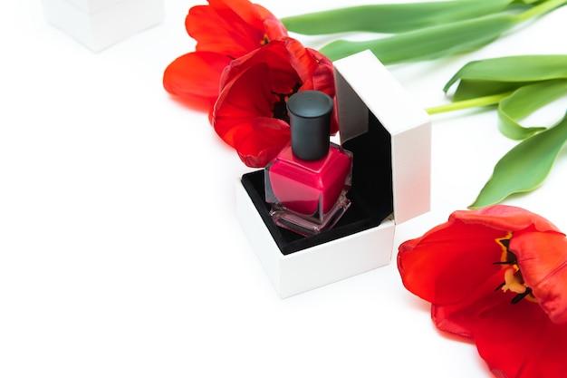 Botella de esmalte de uñas rosa y flores de tulipán sobre fondo blanco.