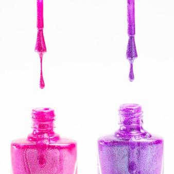 Botella de esmalte de uñas rosa y púrpura sobre fondo blanco