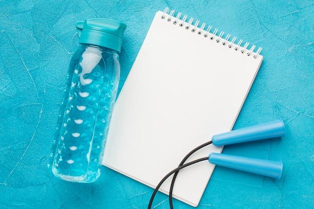 Botella de fitness vista superior y bloc de notas de espacio de copia