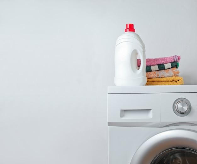 Botella de gel de lavado y pila de toallas en la lavadora.