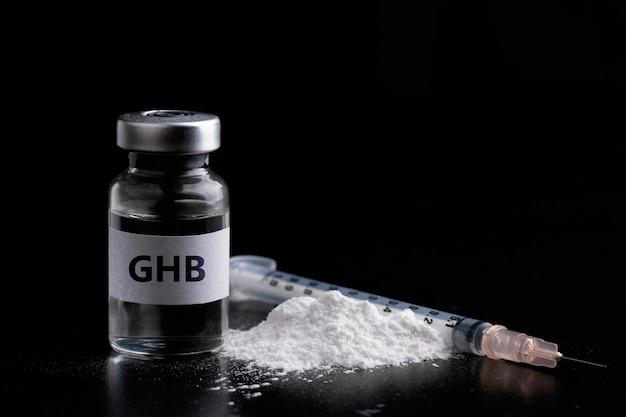 Botella de ghb con una jeringa en droga negra peligrosa