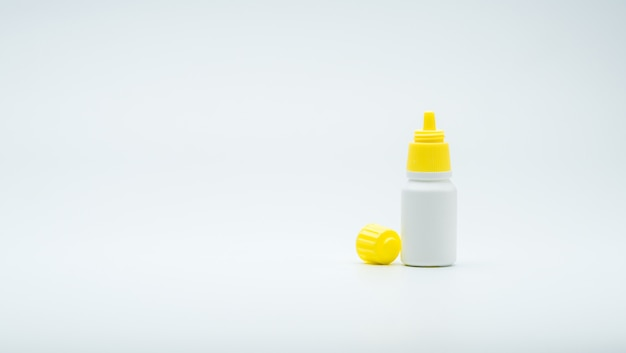 Botella de gotas para los ojos con tapa amarilla abierta aislada sobre fondo blanco con etiqueta en blanco y copia espacio, solo agregue su propio texto.