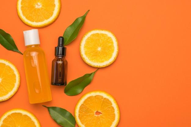 Una botella con un gotero y una botella de jugo de naranja sobre naranja con hojas verdes.