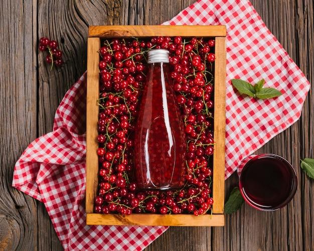 Botella de jugo de arándano sobre fondo de madera
