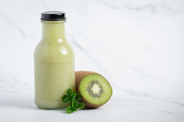 Botella de jugo de kiwi en piso blanco