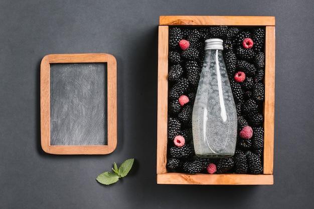 Botella de jugo de zarzamora en espacio de copia de caja de madera