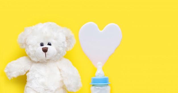 Botella de leche para bebé con juguete oso blanco sobre fondo azul.