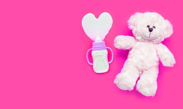 Botella de leche para bebé con osito blanco sobre superficie rosa.