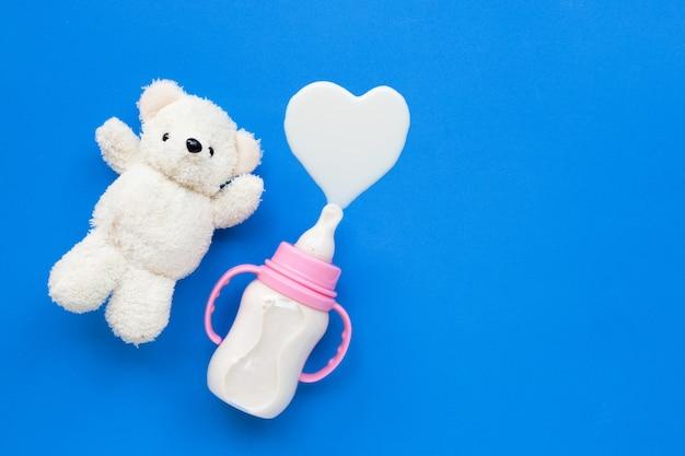 Botella de leche para bebe con oso de juguete blanco sobre azul.