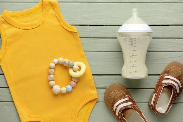 Botella de leche para bebé con ropa sobre fondo de color