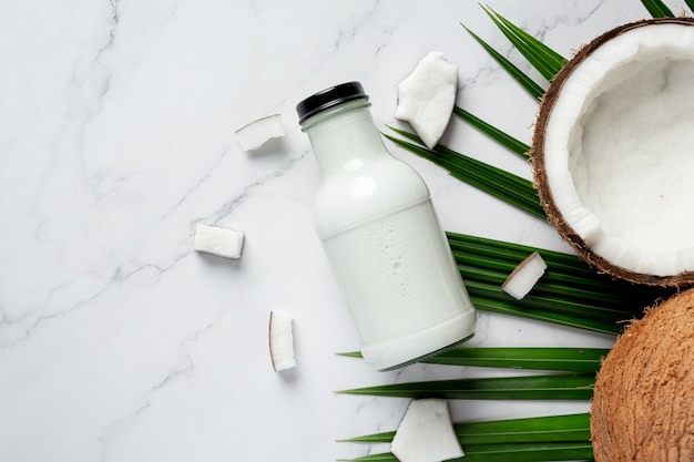 Botella de leche de coco sobre fondo de mármol blanco