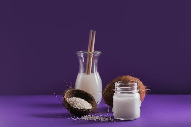 Botella de leche de coco vegana, aceite de coco, coco entero y hojuelas sobre mesa violeta. concepto de comida sana y alimentación limpia.