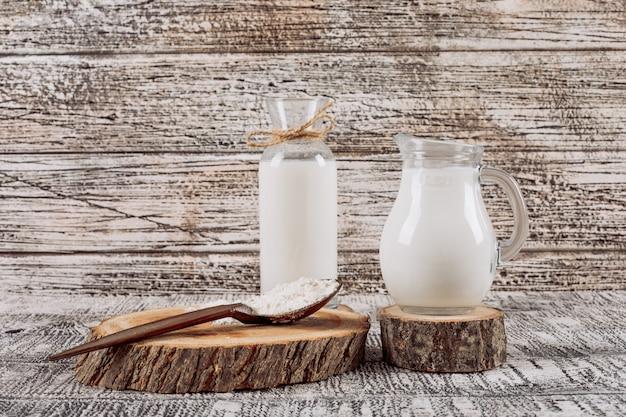 Botella de leche con jarra de leche sobre una rodaja de madera, cuchara de madera vista de ángulo alto sobre un fondo blanco de madera