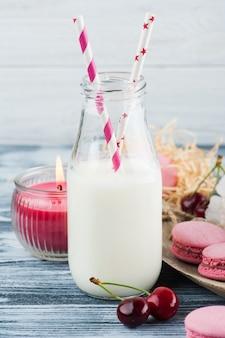 Botella de leche con macarrones rosados franceses