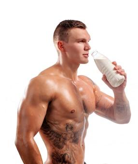 Botella de leche en manos de deportista, hombre sano. tatuaje