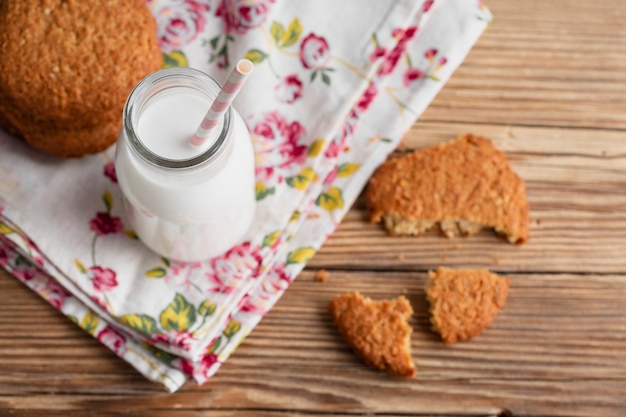 Botella de leche con paja y galletas.