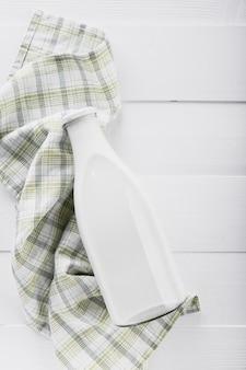 Botella de leche plana con toalla de cocina
