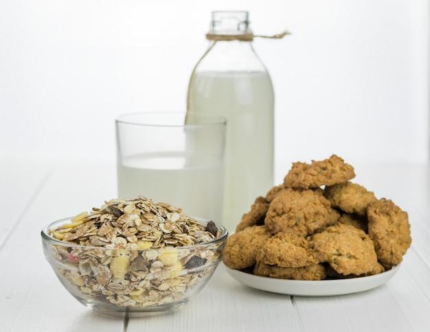 Botella de leche, tazón con muesli y galletas recién horneadas en una mesa de madera blanca.